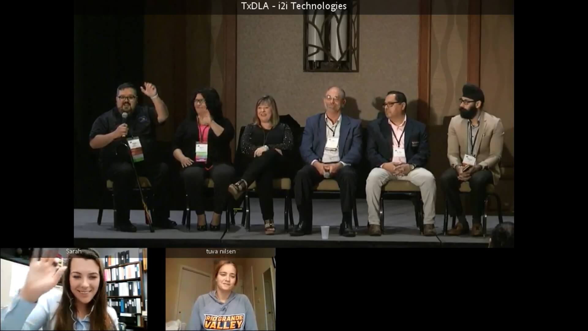 Five people sitting on a stage and two other students connecting via Zoom