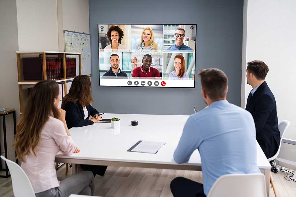 Corporate meeting room with distance learning video conference on the wall.